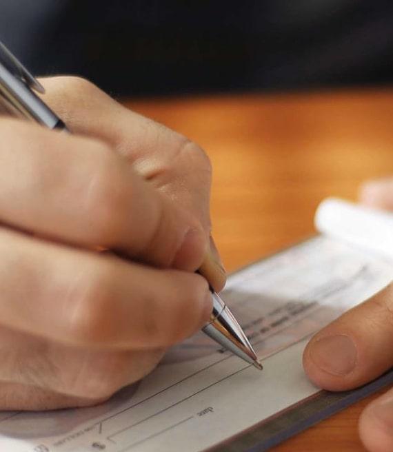 Mano firma assegno con penna d'argento
