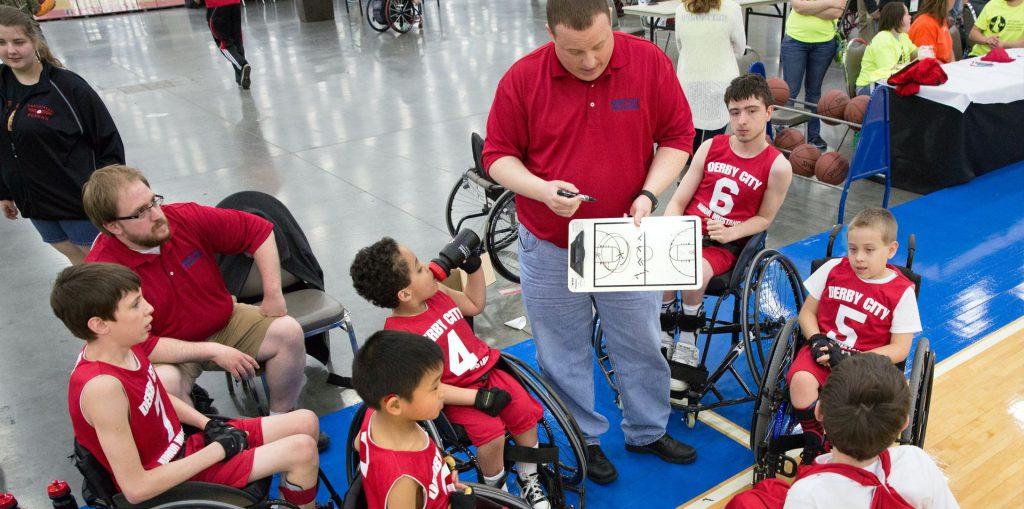 Coach di basket parla con bambini disabili