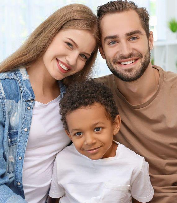 Coppia di ragazzi sorridente con bambino adottato
