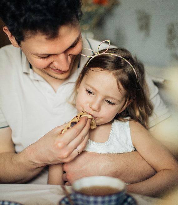Papà fa mangiare biscotto alla sua bambina