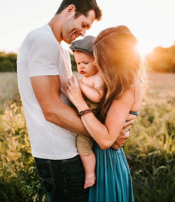 Papà e mamma in una prateria abbracciano neonato col cappellino