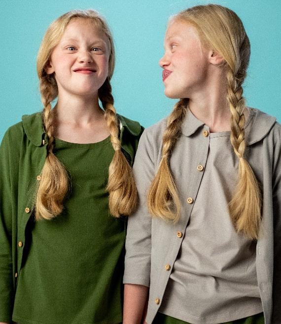 Due bambine gemelle bionde si guardano facendo facce buffe