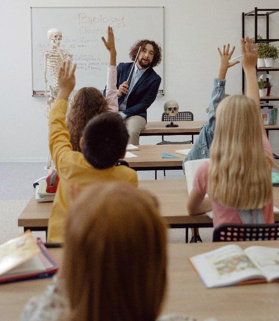 Professore biologia interroga bambini mani alzate