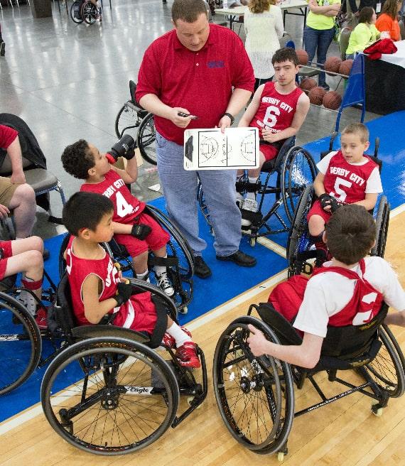 coach con un gruppo di bambini seduti sulla sedia a rotelle