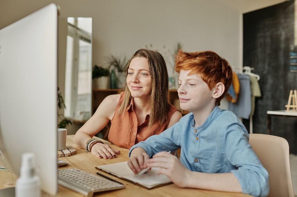 Donna e bambino sorridenti guardano schermo computer